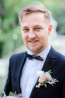 Handsome groom in black suit and white rose boutonniere stands in the garden
