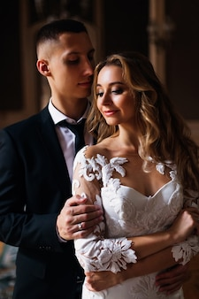Handsome groom in black suit with tie hugging beautiful bride in white dress. close up.