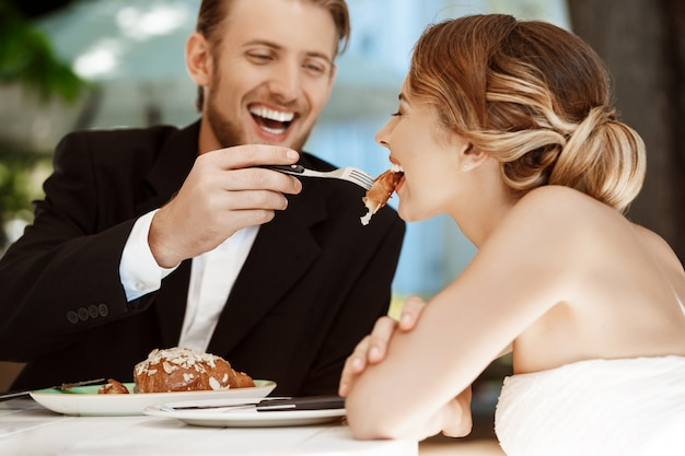 Handsome groom feeding his bride with croissant in cafe.