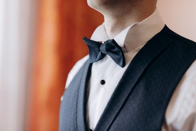 ハンサムな新郎が服を着て結婚式の準備