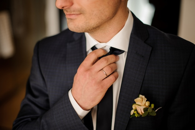 Handsome groom getting dressed in wedding suit with boutonniere