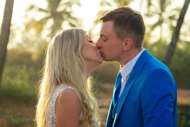 Красивый жених в шикарном костюме и красивая невеста в красивом свадебном платье, улыбаясь на фоне пальм. концепция шикарной и богатой свадебной церемонии на пляже
