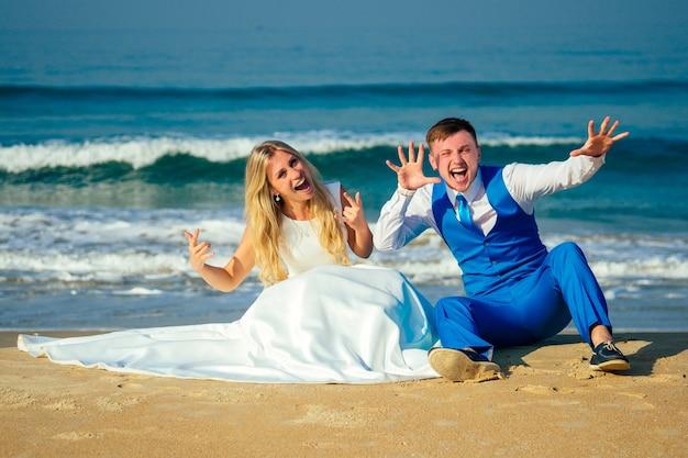 シックなスーツを着たハンサムな新郎とウェディングドレスを着た美しい花嫁がビーチの砂の上に座っています。ビーチでのシックで豊かな結婚式のコンセプト。