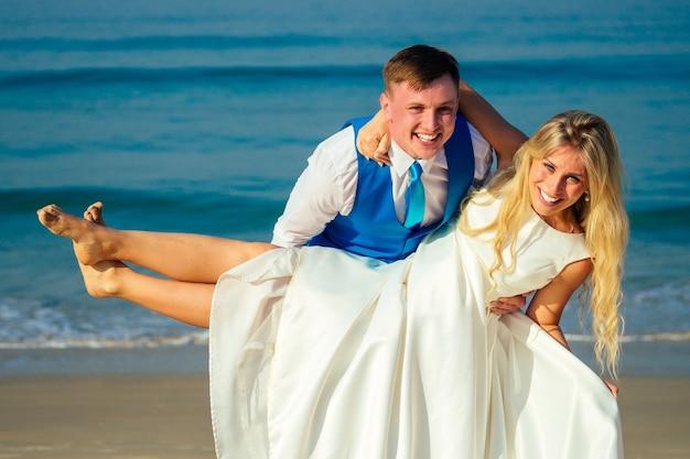 シックなスーツを着たハンサムな新郎は、ウェディングドレスを着た美しい花嫁を抱いていて、ビーチで楽しんで顔をゆがめています。ビーチでのシックで豊かな結婚式のコンセプト。
