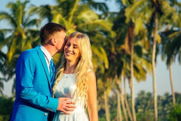 Красивый жених в роскошном костюме и красивая невеста в красивом свадебном платье улыбается и позирует на фоне пальм. концепция шикарной и богатой свадебной церемонии на пляже