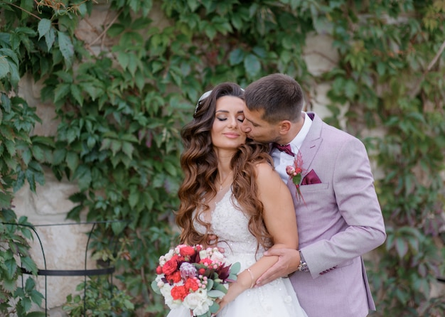 ハンサムな新郎がおしゃれな結婚式の服装に身を包んだ屋外で美しい花嫁にキスします。