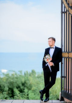 Handsome groom leans to the gates standing before a great sea view
