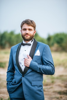Handsome groom in wedding suit posting in the park