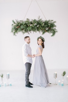 ハンサムな花婿付け添人とかなりの花嫁介添人が手をつないで、結婚式の装飾と白いスタジオに立つ