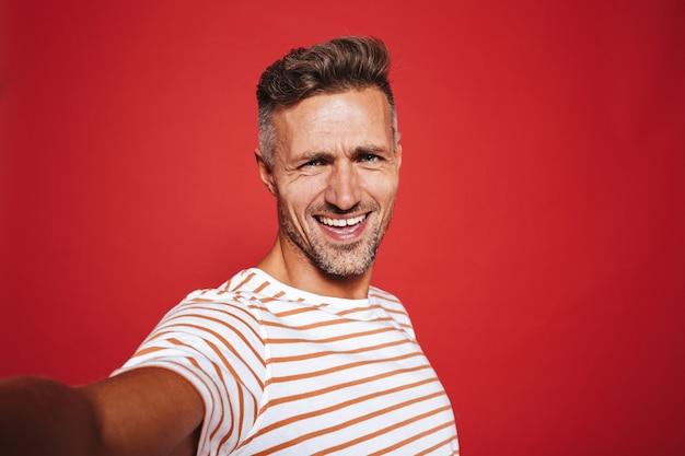 Красивый парень 30-х годов в полосатой футболке улыбается, делая селфи на красном фоне