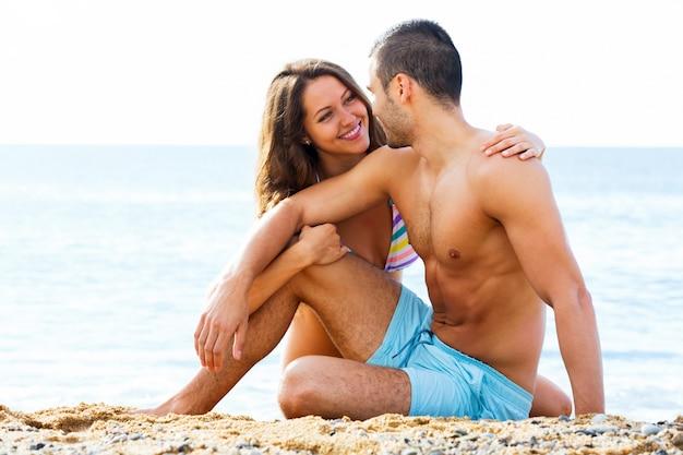 잘 생긴 남자와 예쁜 여자 친구 모래에 휴식