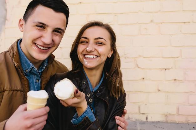 ハンサムな男ときれいな女性がアイスクリームでポーズ