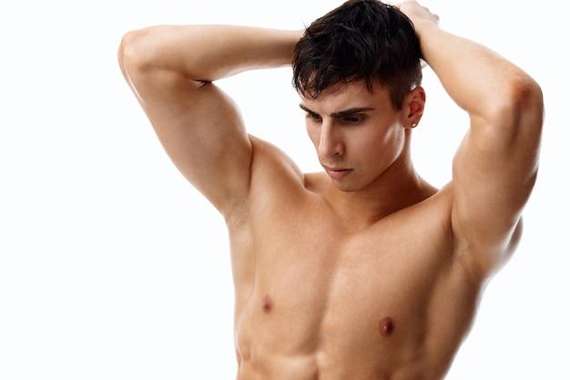 Красивый парень-спортсмен с голым торсом держит руки за головой