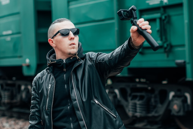 Handsome guy in black clothes and sunglasses making selfie or streaming video using action camera with gimbal camera stabilizer at railway