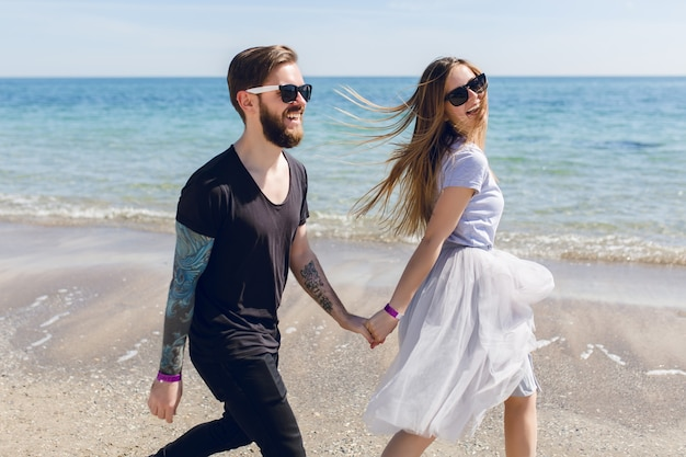 Handsome guy in black sunglasses with beard walks on the beach near sea holding a hand of pretty woman with long hair