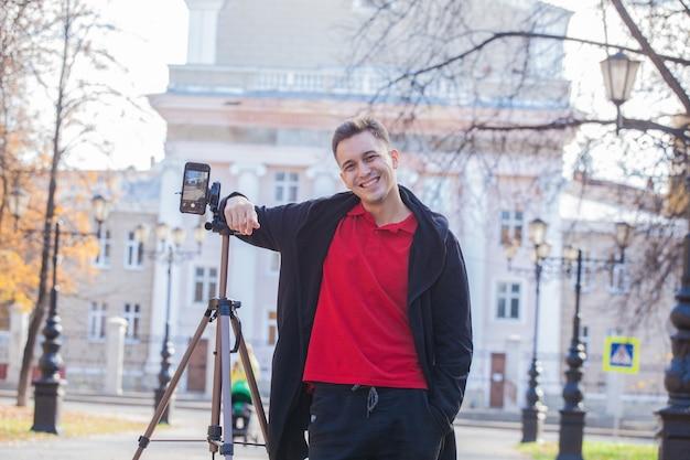 Красивый парень блоггер снимает штатив на улице