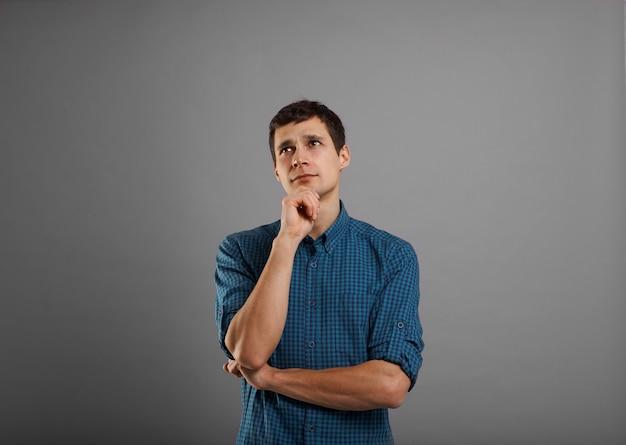 Bel ragazzo in camicia blu pensando