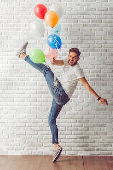 Handsome guy in casual clothes holding balloons