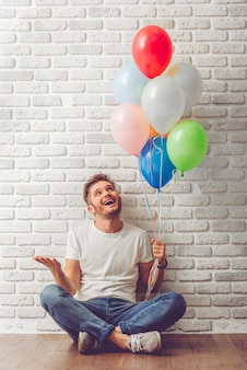 Handsome guy in casual clothes is holding balloons.