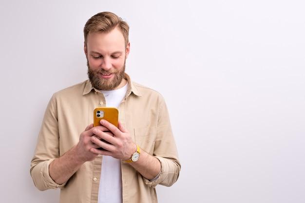 스마트 폰에서 누군가와 채팅하는 잘 생긴 남자, 즐거운 미소를 지으며, 흰 벽에 고립 된 포즈, 초상화
