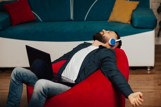 目を閉じて肘掛け椅子に座って、ヘッドフォンで音楽を楽しんでいるハンサムな男。
