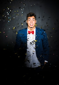 Handsome guy in evening jacket between confetti