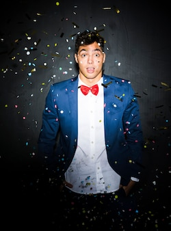Handsome guy in evening jacket between tossing confetti
