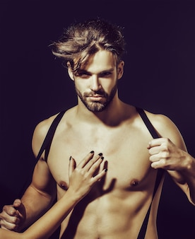 Handsome guy fashion sexy young bearded macho man model with suspenders on pants with female hand on bare muscular torso holds on grey surface
