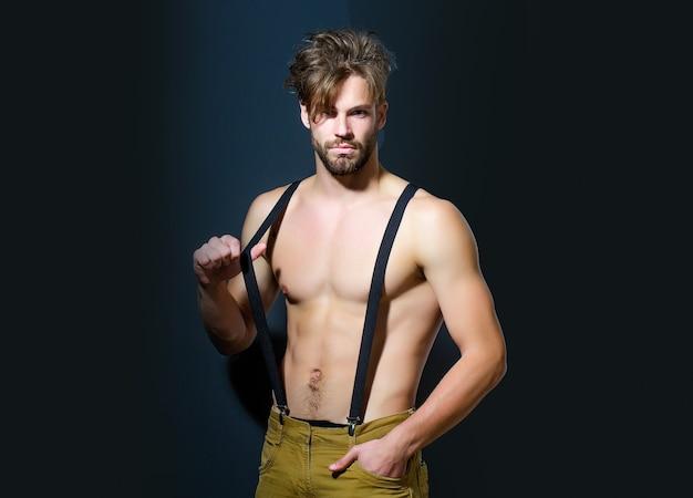 바지와 벌거 벗은 근육질의 몸통에 멜빵이있는 잘 생긴 남자 패션 섹시한 젊은 남자 모델