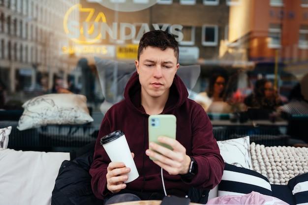 Красивый парень гуляет и отдыхает в летнем кафе