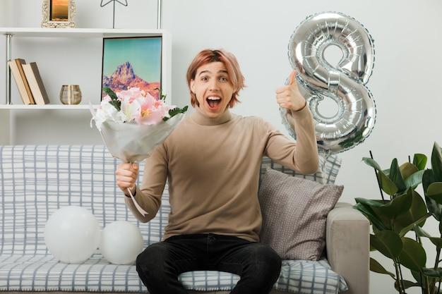 Bel ragazzo in una felice giornata delle donne con in mano un bouquet seduto sul divano in soggiorno