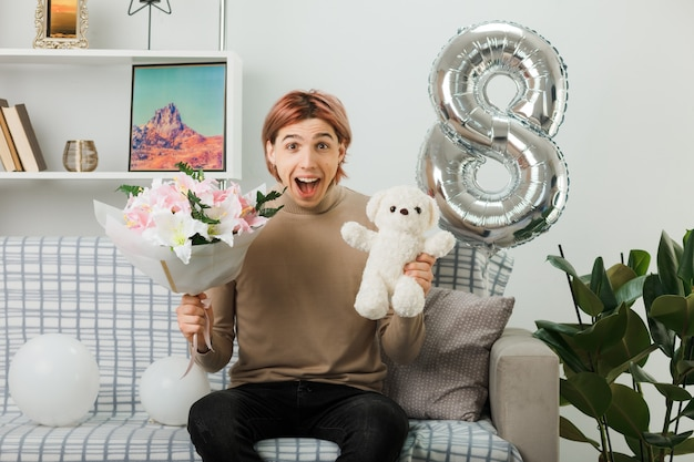 Handsome guy on happy women day holding bouquet with teddy bear sitting on sofa in living room