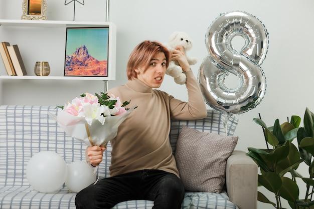 Bel ragazzo in una felice giornata delle donne che tiene in mano un bouquet con un orsacchiotto seduto sul divano in soggiorno