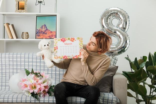 Bel ragazzo in una felice giornata delle donne che tiene e guarda l'orsacchiotto con il calendario seduto sul divano nel soggiorno
