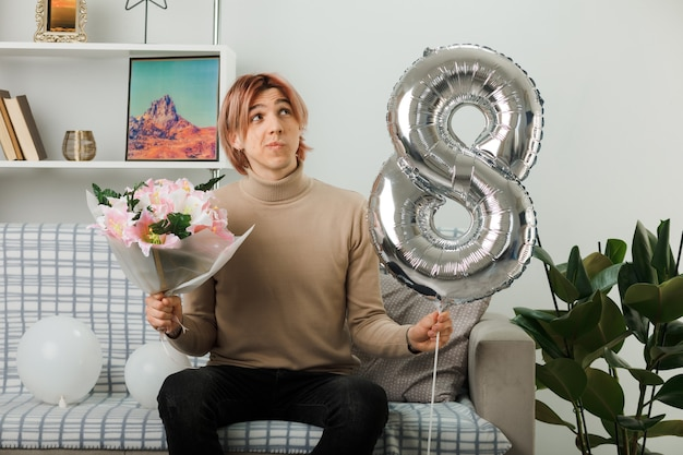 Handsome guy on happy women day holding number eight balloon and bouquet sitting on sofa in living room