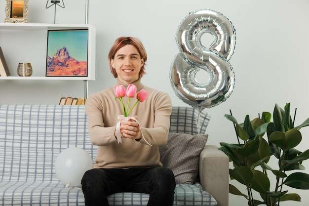 Handsome guy on happy women day holding out flowers at camera sitting on sofa in living room
