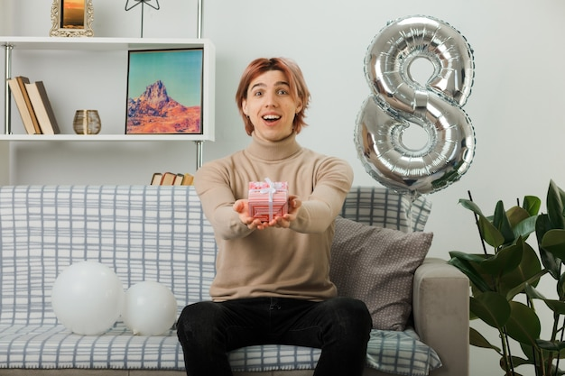 Handsome guy on happy women day holding out present at camera sitting on sofa in living room