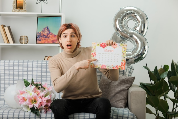Bel ragazzo in una felice giornata delle donne che tiene e indica il calendario seduto sul divano nel soggiorno