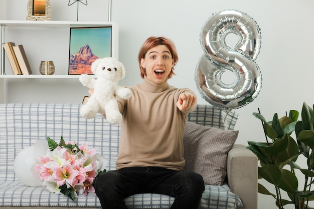 Bel ragazzo in una felice giornata delle donne che tiene orsacchiotto seduto sul divano in soggiorno
