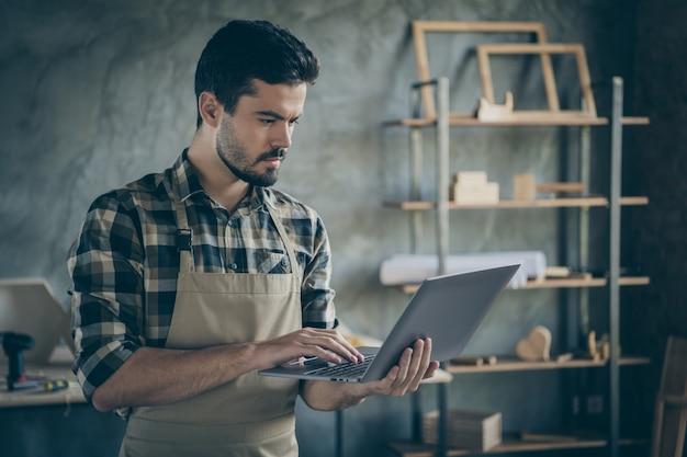 Красивый парень держит ноутбук, смотрит онлайн видео мастер-класс имеет бесплатное самообразование сфокусированный деревянный бизнес промышленность столярка гараж в помещении