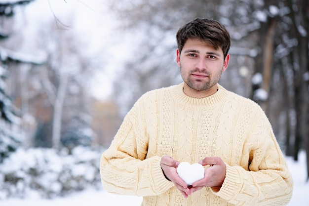 Красивый парень держит сердце из снега