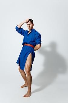 完全な成長のゲイモデルの明るい背景に青いドレスを着たハンサムな男