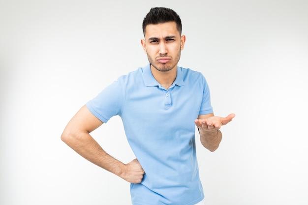 Красивый парень в синей футболке предлагает свою идею на белом фоне студии.