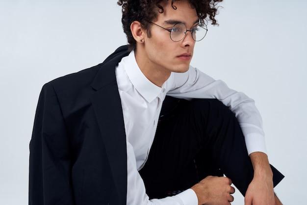 明るい部屋の写真スタジオモデルの髪型巻き毛のジャケットとシャツとメガネのハンサムな男