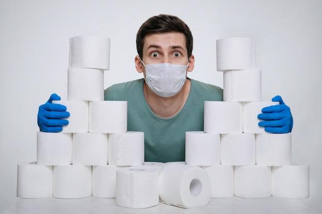 코로나 바이러스 감염을 방지하기 위해 화장지 벽 뒤에 숨어있는 보호 얼굴 마스크와 의료 장갑에 잘 생긴 남자