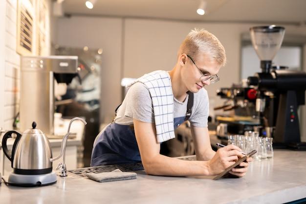 Красивый парень в фартуке и футболке просматривает заказы в своем блокноте в начале рабочего дня в кафетерии
