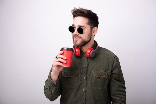 선글라스와 헤드폰을 끼고 흰 벽에 커피 한 잔을 들고 있는 잘생긴 남자