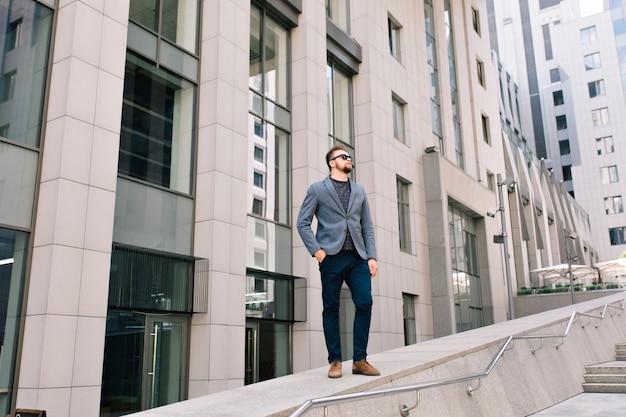 サングラスでハンサムな男が通りに立っています。