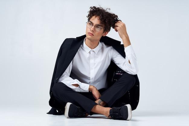 明るい部屋と巻き毛のズボンのシャツとジャケットとスニーカーのハンサムな男