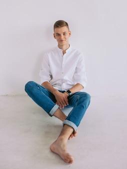 실내 바닥에 앉아 흰 셔츠와 청바지에 잘 생긴 남자